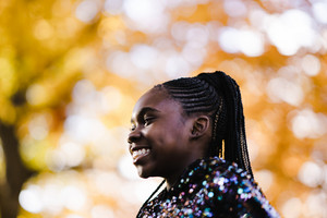 black girl wearing glittery jacket smiling outside in autumn