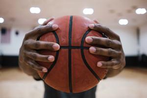 black hands gripping a basketball