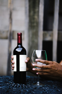 black hands holding a bottle of wine and a wine glass on a table