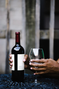 black hands holding a bottle of wine and a wine glass