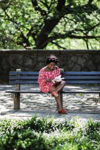 Black lady sitting on a park bench reading a book