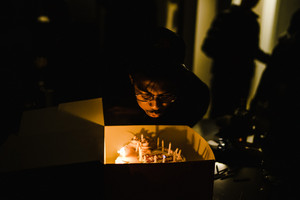 black man blowing out birthday candles on cake