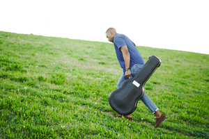 black man carrying guitar case uphill