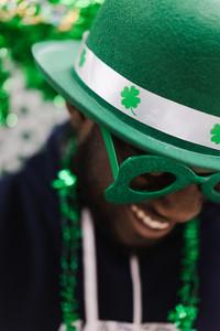 black man celebrating St. Patrick's Day in green glasses and hat