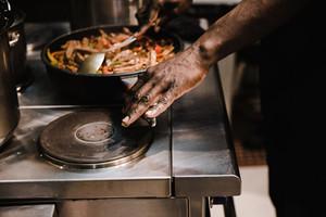 Black man cooking food on stove