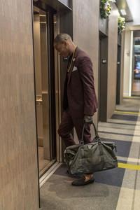 black man enters elevator door in a hotel
