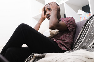 Black man grabbing head in confusion during therapy session