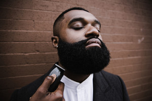 Black man having his beard trimmed with eyes closed and chin out