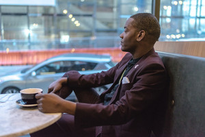 black man in a suit drinks coffee and looks outside window