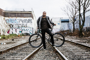black man in front of bicycle train tracks graffiti