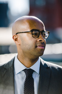 black man in suit and glasses looks off into distance