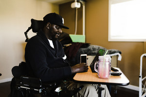 black man in wheelchair sitting at table watching tablet