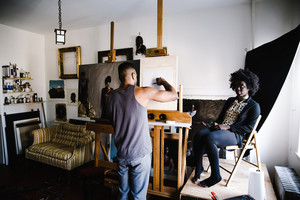 black man painting black woman in art studio