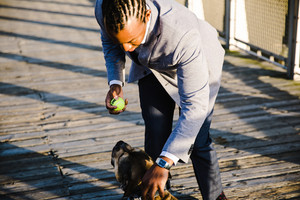Black man playing with his dog