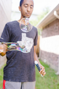 Black man plays with bubbles outside as he celebrates an American holiday