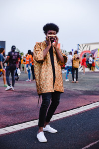 Black man posing in traditional African attire at music festival
