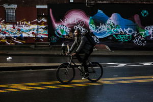 black man riding bicycle on road in front of grafitti