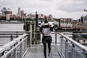 Black man running on pier around water