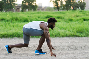 Black man setting up to run