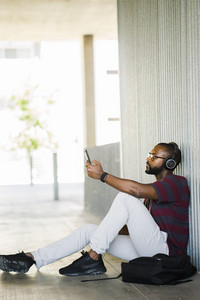 Black man sitting outside on a phone