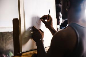 Black man sketching in detail