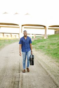 black man smiling while carrying guitar case outside