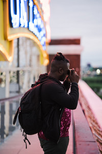 black man taking photo outside in front of neon light
