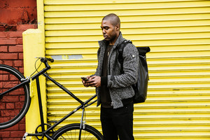 black man typing on cell phone bicycle yellow garage red brick wall
