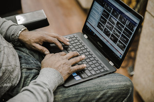 Black man typing on Chromebook computer
