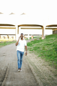 black man walking and talking on phone outside while smiling