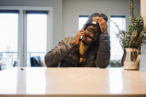 black man wearing glasses and coat talking on the phone and laughing