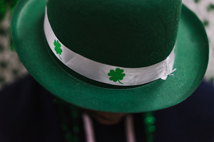 Black man wearing green St. Patrick's Day leprechaun hat with four leaf clovers