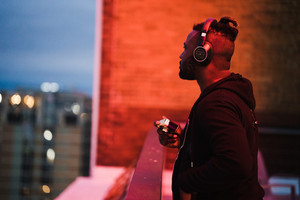 black man wearing headphones and holding camera at night