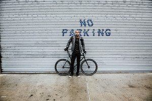 black man with bicycle in front of garage no parking sign
