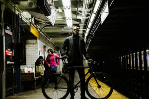 black man with bicycle in subway station people in background shopping bags