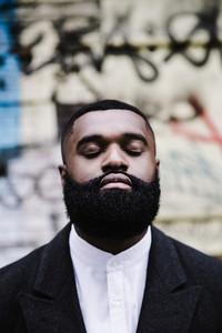 Black man with eyes closed thinking close up