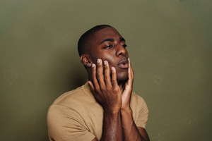Black man with hands on face and eyes closed thinking