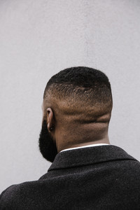 Black man with his back of the head towards the camera