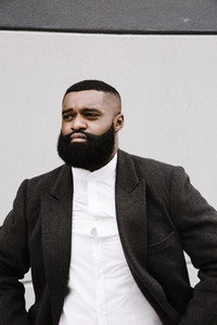 Black man with his coat open in a white background picture