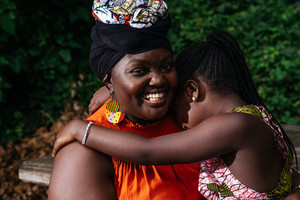 Black mother laughing with daughter