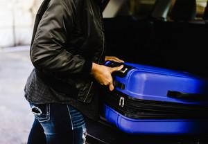 Black person putting their luggage in their car