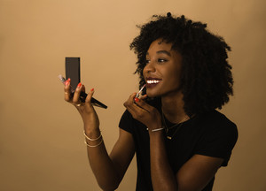black woman applies lipstick with a compact mirror