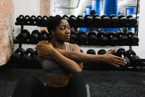 black woman doing arm stretches in weight room or gym