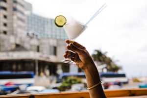 black woman holds blended cocktail in the air