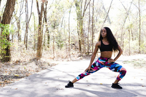 Black woman in athletic clothing doing a workout in a park