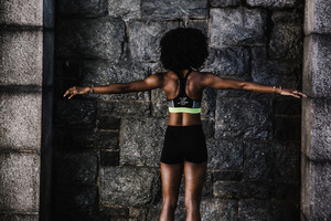 Black woman in athletic shorts and sports bra stretches out her arms