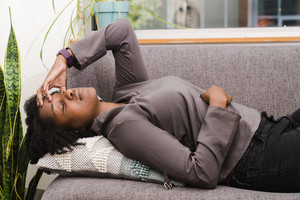 Black woman laughing in therapy session closing her eyes thinking intently