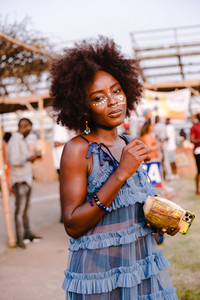 Black woman posing in traditional African attire at music festival