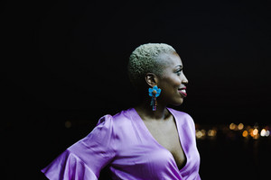 Black woman posing to the side with purple blouse and earrings