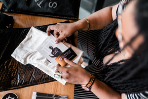 black  woman sitting at table looking at brand materials